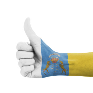 Hand with thumb up, Canary Islands flag painted as symbol of exc